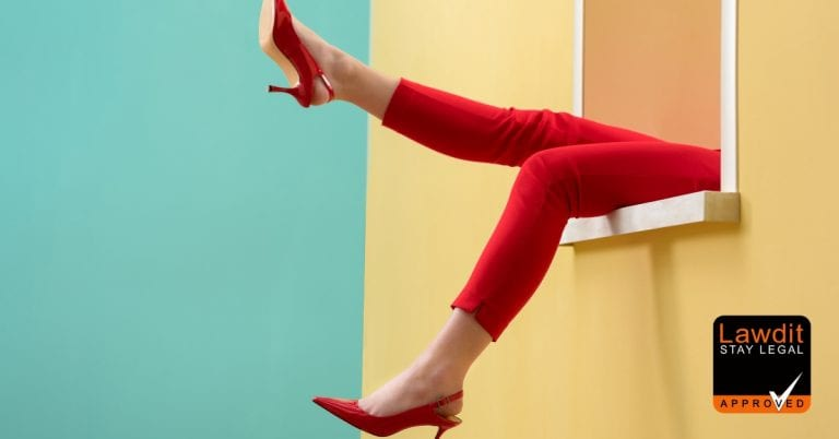 woman wearing red heals and red trousers hanging her legs outside of a window
