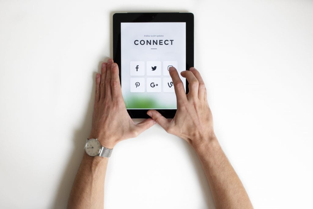 Male hands holding a tablet with social media platform logos and the word connect.   Social media enables intense connection with consumers which is key for marketing your business - after all. consumers and clients are the foundations of all businesses.