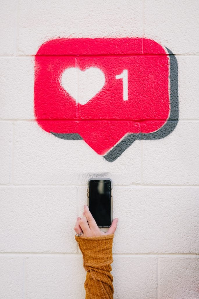 """Hand holding smart phone with a large Instagram """"like"""" heart spray painted on the wall behind. Audience engagement is paramount for growing your business.   Social media enables business organisations to directly connect with customers and consumers just at the right time with low cost and greater efficiency in comparison to other more traditional forms of communication."""