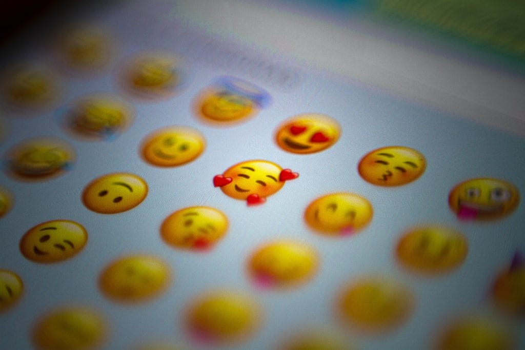 Emoji faces on a mobile phone, how can emojis be used on your business social media.