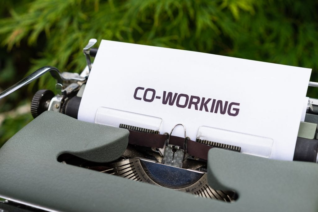 """Image of a typewriter with a sheet of paper on the reel stating """" co-working"""". Co-working and outsourcing social media management nable you to build your brand, client base, and market your business effectively and efficiently without stress and commonly encountered teething pains."""