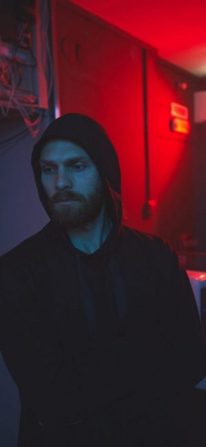 Serious handsome young bearded hacker in hoodie leaving server room with broken Ethernet hub and red light in background