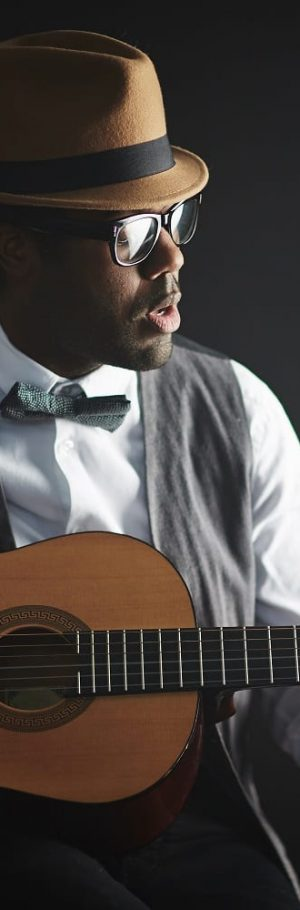 Young African musician playing guitar and singing