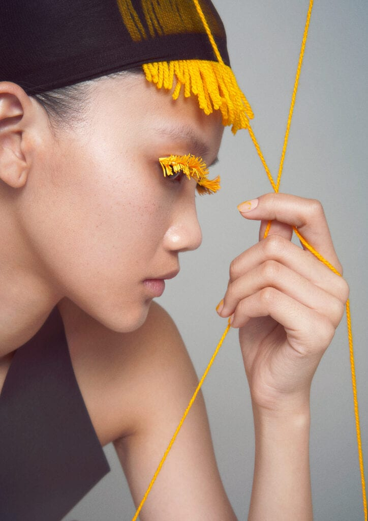 Woman with yellow string hair made of fabric.