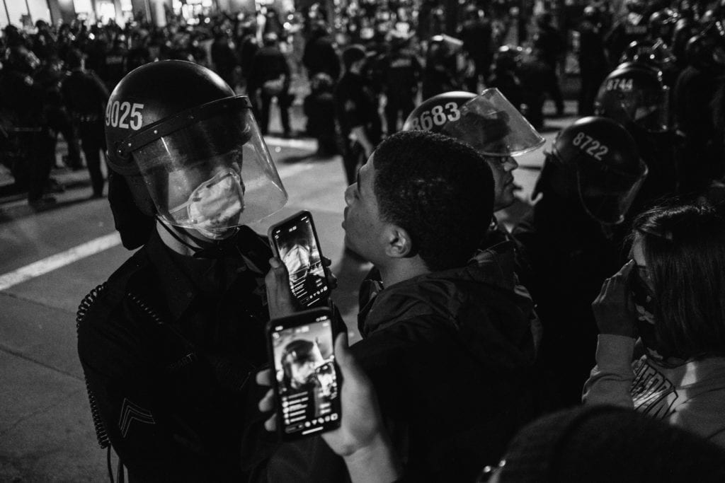 Protestor stands face to face with police