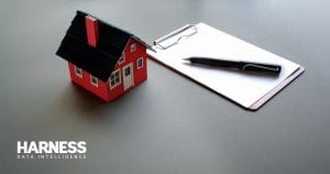 Model house next to a notebook and pen
