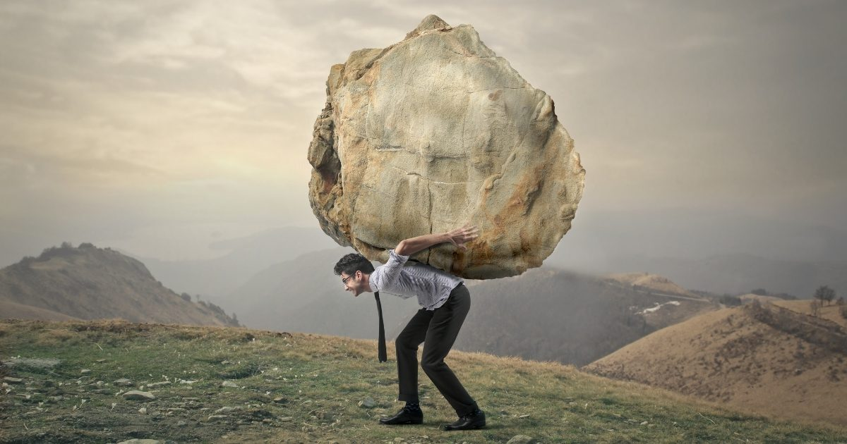 Man carrying a large stone up a mountain